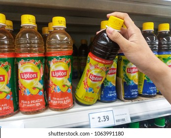 Bukit Tinggi - Klang , Malaysia - 4 April 2018 : Hand pick up a LIPTON plastic bottle drink flavor peach ice tea owned by the company Unilever on the shelves in supermarket. Mobile photoghpy.