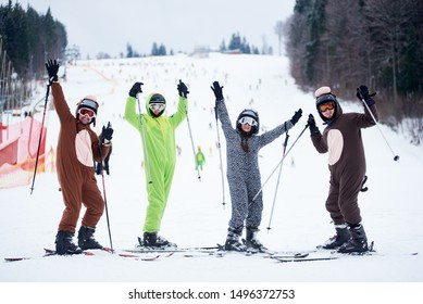 Bukovel, Ukraine - December 09, 2018: skiers men and woman on skis in ski mask dressed in animals costumes, smiling and raising their hands up with ski poles, standing at foot of snowy slope