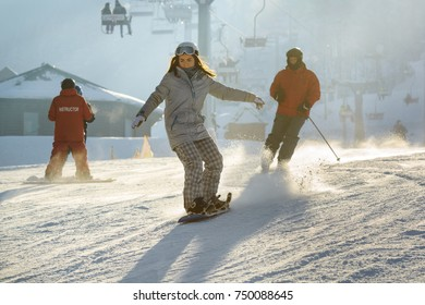 BUKOVEL, UKRAINE, DECEMBER 2016. Concentrating young woman on snowboard on a ski slope illuminated by sun