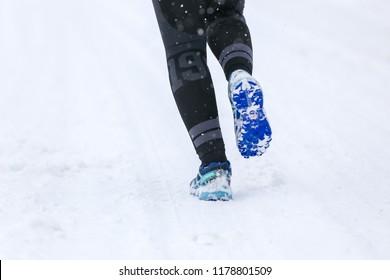 BUKOVEL, UKRAINE - MARCH 20, 2018: Female legs in Salomon speedcross 4 GTX running or jogging on winter road