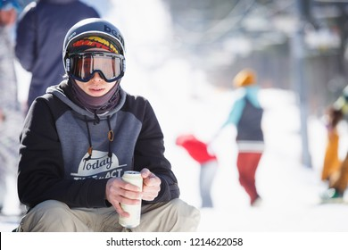 BUKOVEL,UKRAINE-19 MARCH,2018: Portrait of rider boy drinking beverage from can.Winter action sports festival in snow park.Young people compete in big air snowboarding & skiing.Active youth lifestyle