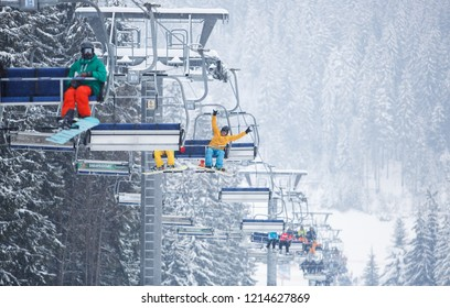 BUKOVEL,UKRAINE-19 MARCH,2018: Ski resort elevator mechanism transport happy snowboarder guy on top of mountain for a ride.Specialized aerial lift or chairlift mounted on rope in winter park