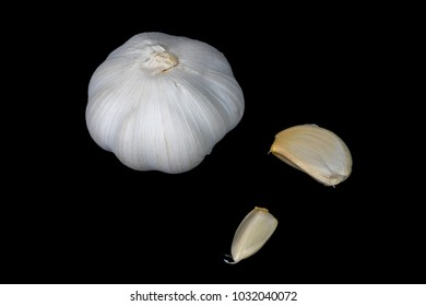 A bulb of garlic and a couple cloves on a black surface.
