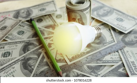 Bulb Light on banknotes background.Concept of saving money and energy.