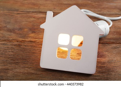 Bulb and shape of home on wooden background