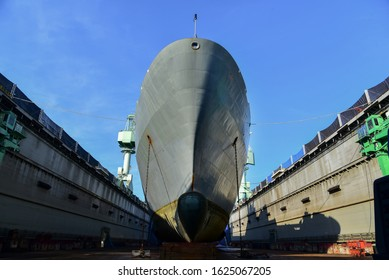 Bulbous bow battleship moored in dock yard during maintenance, low angle image of Front View ship with anchor center forecastle deck of commercial ship floating dock yard in shipyard,