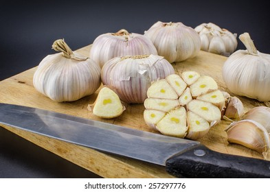 Bulbs of fresh garlic with several cloves on the cutting board. Shallow depth of field.