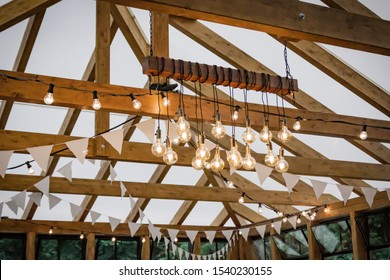 The bulbs hung on a wooden beam shine with warm light. Ceiling decoration of the wedding hall. Boho wedding. Rustic party.