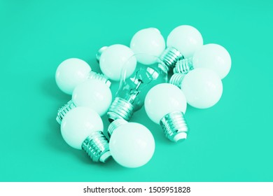 A lot of bulbs in trend mint tonic. Lamps on a mint background. A large set of led bulbs. A burned out incandescent bulb and led energy-saving light bulbs are on the light surface.