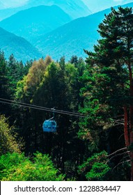 Bulgaria, Bansko - August 25, 2018: Cable-car cabin on a steel cable way, mountains on the background, summertime. Rope way transportation lift, part of ski and snowboarding resort.
