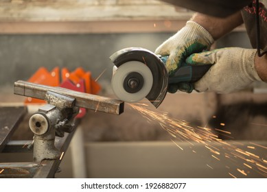 bulgarian angle grinder rotates the disc, a person cuts off the metal profile with his hands, sparks fly, beautiful glow, bokeh, orange light on a black background, production, flash of light
