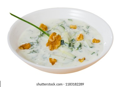 Bulgarian cuisine. Traditional chilled soup Tarator on yogurt with fresh cucumber, dill and walnuts in white plate. Isolated over white background