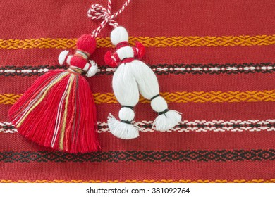 Bulgarian Martenitsa. It is a small piece of adornment, made of white and red yarn. They are worn from Baba Marta Day (March 1) until the wearer first sees a stork or budding tree.
