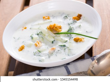Bulgarian Tarator - traditional summer chilled vegetable soup with yogurt, cucumbers, greens, walnuts in white bowl