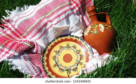 Bulgarian traditional ceramic pottery - clay jug and a plate with traditional ornaments design on white tablecloth, eastern Europe, Plovdiv, Bulgaria, picnic retro, eating outside, festive