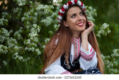 Bulgarian traditional costume- Nosia. Smiling woman in the beautiful nature.