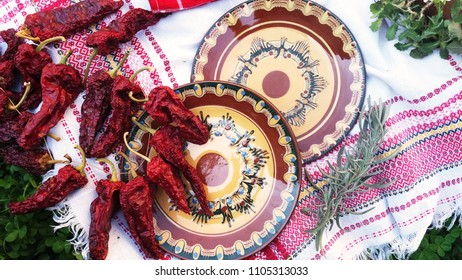 Bulgarian traditional pottery on white tablecloth decorated with dry peppers and rosemary, clay plates with Bulgarian ornaments on a grass background, Bulgarian culture