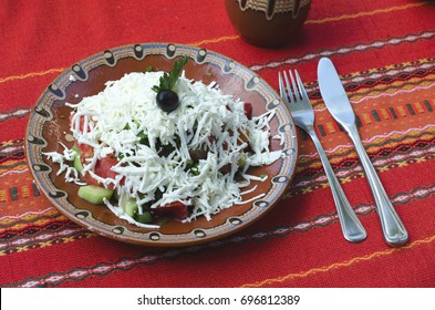 Bulgarian traditional Shopska salad served in a traditional restaurant - mehana. The dish includes the famous white cheese and vegetables.