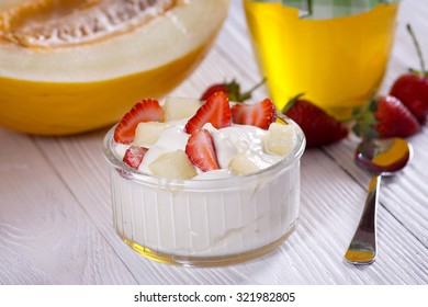 Bulgarian yogurt with strawberries and melon on the table.