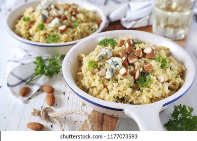 Bulgur cereal risotto with blue cheese, parsley and almonds, two servings in ceramic pans and white wine