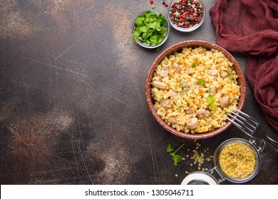 Bulgur with turkey, pork or beef. Eastern dish of rice, delicious traditional food. Stewed meat with grits. Pilaf on dark background. Copy space