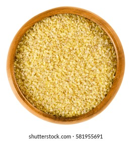 Bulgur in wooden bowl. Uncooked cereal food, most often made from groats of durum wheat. Also called burghul, a kind of dried cracked wheat. Isolated macro food photo close up from above over white.