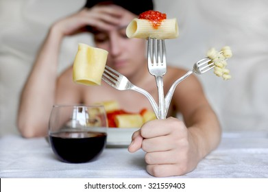Bulimia. Young woman eating macaroni with a triple fork.