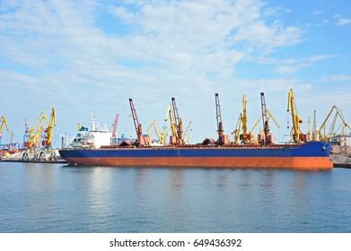 Bulk cargo ship under port crane bridge,
