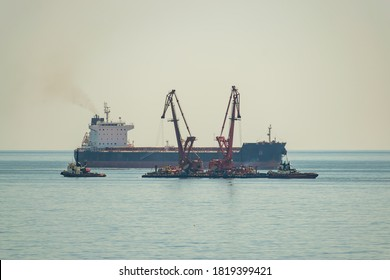 Bulk carrier and floating cranes in harbor near the port