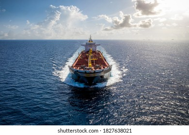A bulk carrier freight ship traveling on full motion over blue sea