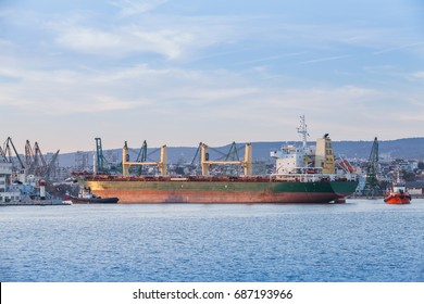 Bulk carrier, industrial ship with deck cranes loading in port of Varna, Bulgaria