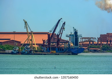 Bulk carrier ship loading bauxite aluminum ore at a loading jetee in the Kamsar port, Guinea, West Africa.