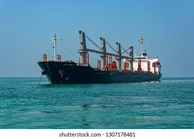 Bulk ore carrier vessel is awaiting loading of bauxite ore from feeders at outer anchorage of Kamsar port, Guinea, West Africa.