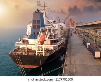 Bulk Vessel alongside at thailand port and discharging steel coil  by  ship's crane.