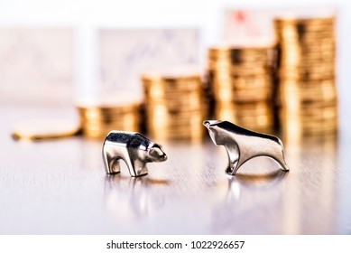 Bull and bear with stacks of coins and stock prices in the background
