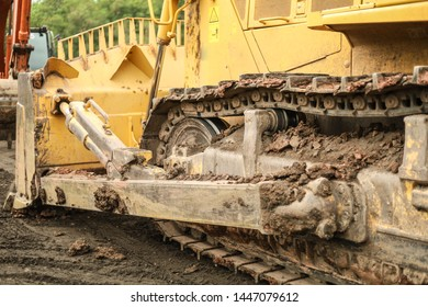 Bull dozer tread with caked mud and dirt