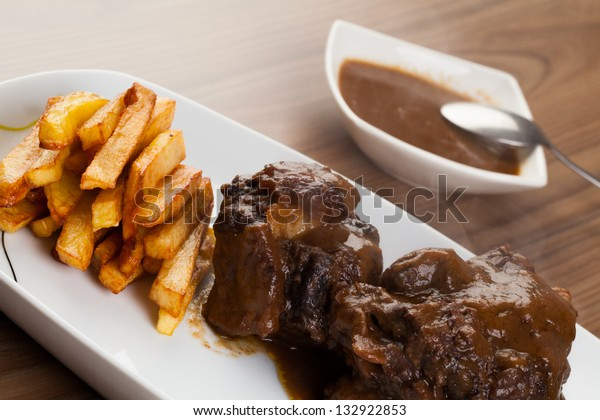 Bull tail dish with fried potatoes. Spanish tapas. Wooden background.
