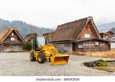 Bulldozer beside house at Shirakawago,Japan.