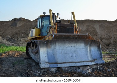 Bulldozer with bucket for pool excavation and utility trenching. Dozer during demolition concrete and asphalt at construction site. Earth-moving equipment for land clearing and foundation digging.