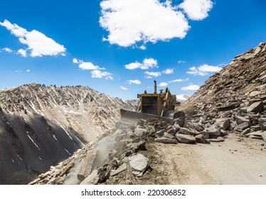 Bulldozer clearing up rocks on the road to Khardung La pass in Ladakh, India. This is the highest motorable road in the world.