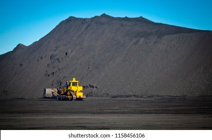 Bulldozer in coal mine, Yellow digger moves coal in front of large pile of coal. Fossil fuel industry, Environmental challenge.
