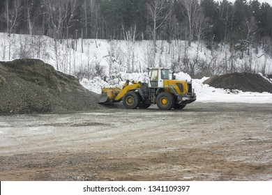 Bulldozer collects gravel scoop in a pile