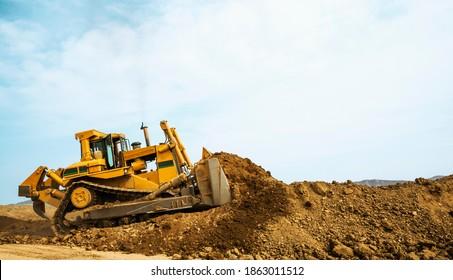 Bulldozer at a construction site shovels mountain soil into a heap