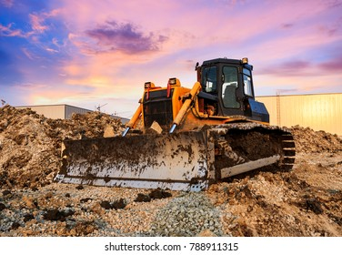 bulldozer at construction site and sunrise landscape