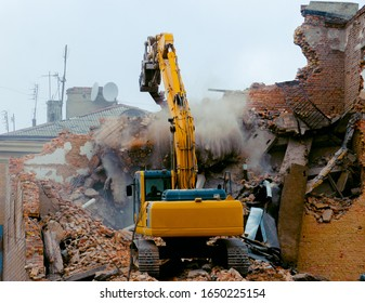 A bulldozer destroys an old building. The concept of the demolition of a building under construction of a new house. Dismantling an old house