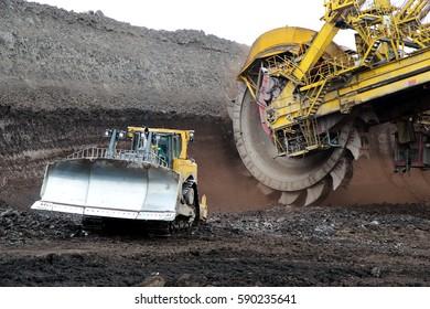 bulldozer and huge mining excavator wheel in brown coal mine