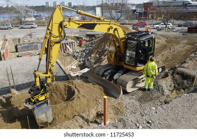 bulldozer inside construction site with hard-hat workers