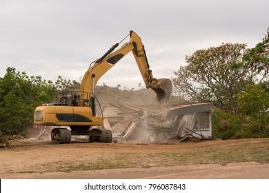 Bulldozer knocking down old house to rebuild