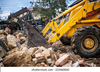 bulldozer loading demolition debris and concrete waste for recycling at construction site