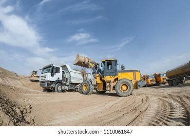 bulldozer loads clay gravel in the truck